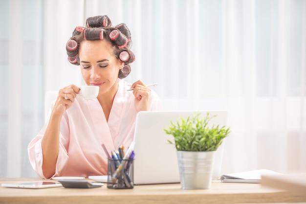 Une femme avec des bigoudis et une chemise de nuit sent le café alors qu'elle est assise devant l'ordinateur à la maison.