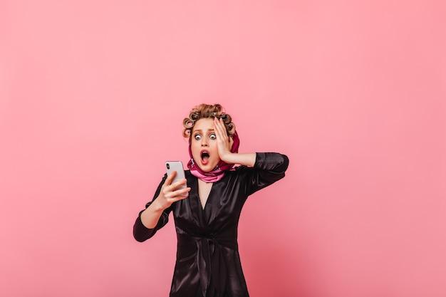 Femme avec des bigoudis regarde avec horreur dans le téléphone