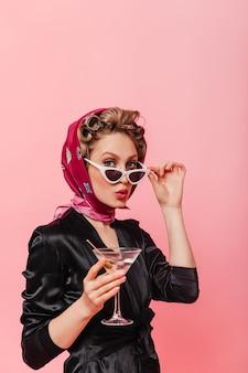 Femme avec des bigoudis sur la tête enlève les lunettes et regarde à l'avant