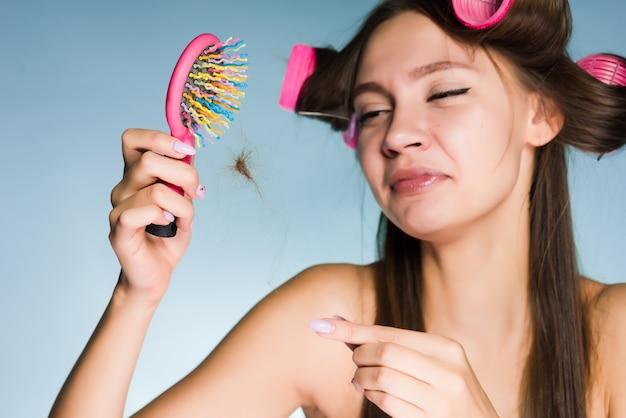 Une femme avec des bigoudis sur la tête est contrariée par la perte de cheveux tenant un peigne dans ses mains