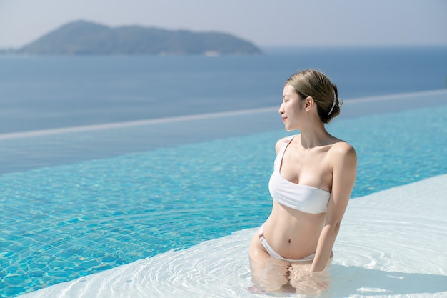 Femme en bikini blanc se détendre au bord d'une piscine à débordement avec vue sur la mer bleue.