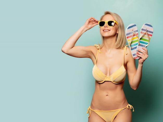 Femme en bikini jaune et lunettes de soleil avec des tongs