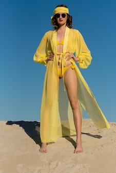 Femme de bikini de maillot de bain de mode dans des maillots de bain chauds marchant sur la destination de plage de vacances de voyage de luxe