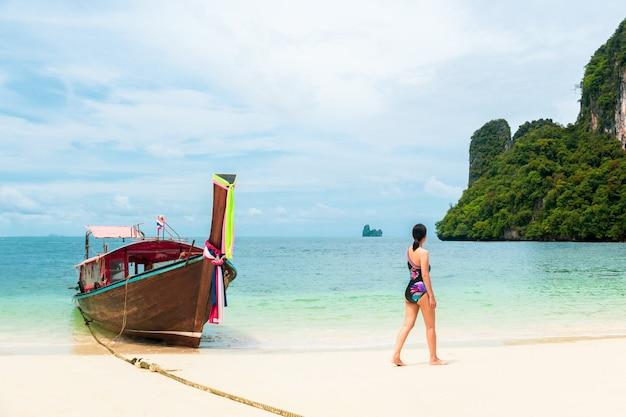 Femme, bikini, marcher, plage, à, bateau longue queue, dans, île tropicale