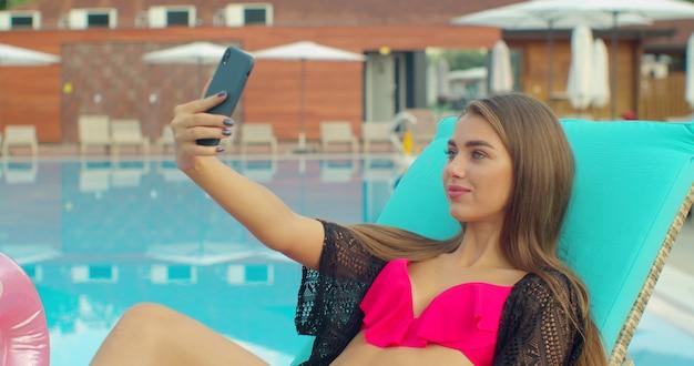 Femme en bikini prenant selfie photo sur la piscine, vacances d'été