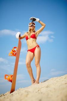 Femme en bikini rouge et snowboard