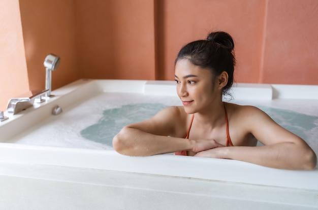 Femme en bikini se détendre dans une baignoire