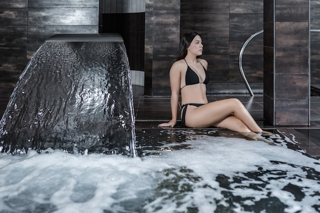 Femme en bikini se détendre dans la piscine spa
