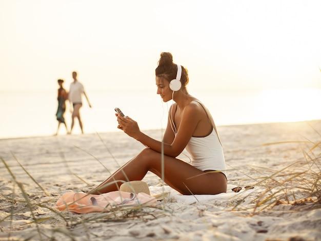 Femme en bikini avec un smartphone et un casque sur la plage