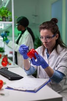 Femme biologiste examinant le poivre écrit l'expertise médicale en microbiologie