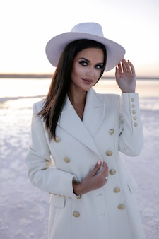 Femme en blanc les femmes avec des chaussures d'hiver fille européenne en manteau souriant par une journée froide enthousiaste femme aux cheveux blonds s'amusant pendant la séance photo d'hiver lac d'hiver sur la neige bottes chaudes hat