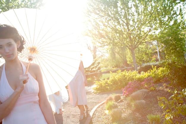 Femme en blanc avec un parapluie en papier