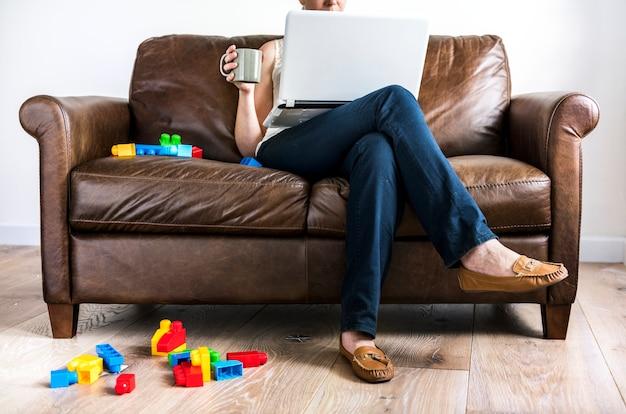Femme blanche à l'aide d'un ordinateur portable sur le canapé
