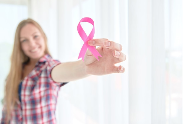 Femme blanche caucasienne tenant un ruban rose sensibilisation au cancer du sein pour le concept de campagne du mois de sensibilisation au cancer du sein.