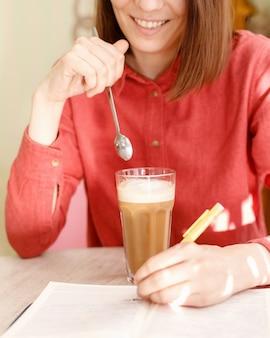 Une femme blanche dans une chemise rose sourit et tient une tasse de café avec ses mains dans un café