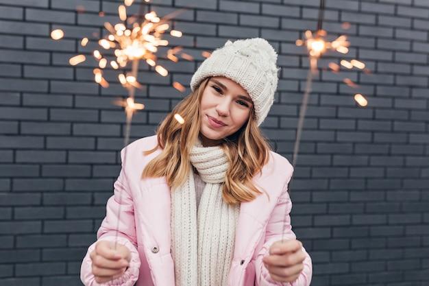 Femme blanche fascinante en tenue d'hiver mignonne posant avec des cierges magiques. plan extérieur d'une fille adorable debout dans une rue urbaine avec des lumières du bengale.