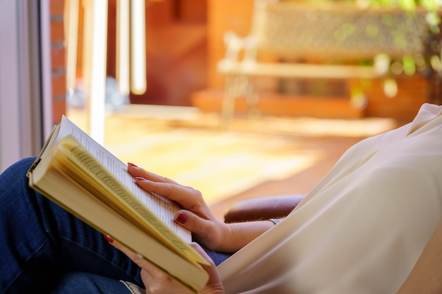 Femme blanche lisant un livre dans un fauteuil se détendre dans une belle lumière du jour à l'extérieur. copiez l'espace.