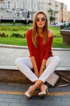 Femme blanche à la mode en pull assis dans la rue dans le centre-ville. lunettes de soleil élégantes. ambiance d'automne.