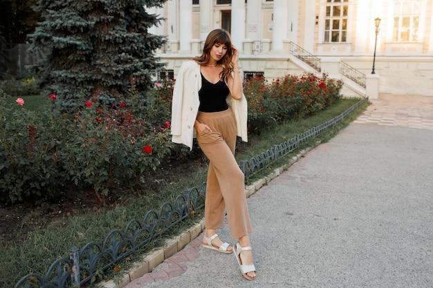 Femme blanche à la mode en veste posant dans la rue. poils ondulés, maquillage naturel. longueur totale.