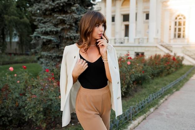 Femme blanche à la mode en veste posant dans la rue. poils ondulés, maquillage naturel.