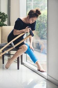 Femme blessée avec attelle de jambe assise et béquilles en bois à l'hôpital
