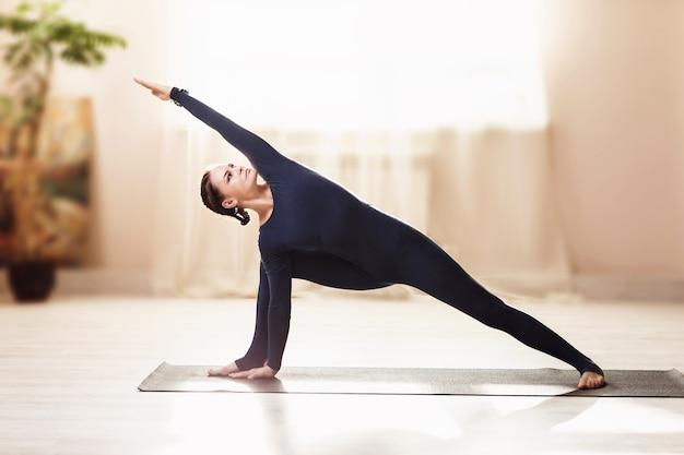 Femme en bleu sportswear pratiquant le yoga faisant de l'exercice uttkhita parshvakonasana dans un appartement près de la fenêtre