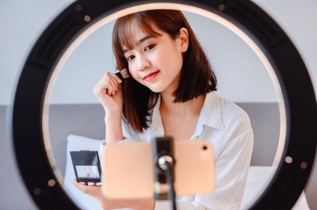 Femme bloguant en ligne et diffusant en direct. un entrepreneur asiatique utilise les médias sociaux pour ses affaires à la maison. nouveau mode de vie normal et distanciation sociale.