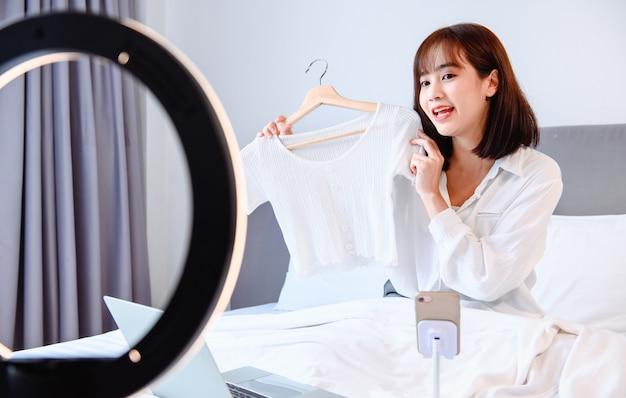 Femme bloguant en ligne et diffusant en direct. un entrepreneur asiatique utilise les médias sociaux pour ses affaires à la maison.