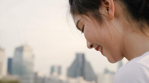 Femme de blogueur de tourisme asiatique joyeuse à l'aide de smartphone pour la direction et à la recherche sur la carte de localisation lors d'un voyage dans la rue au centre-ville.