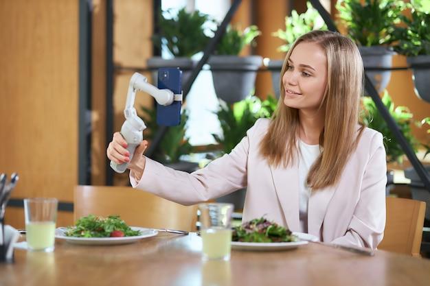 Femme blogueuse faisant selfie et manger de la nourriture délicieuse