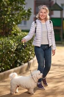 Femme blonde adulte marchant avec un chien blanc moelleux dans le parc de la ville.