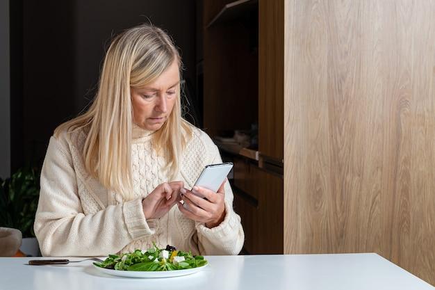 Femme blonde d'âge moyen à l'aide de smartphone tout en mangeant de la salade dans la cuisine, concept de mode de vie