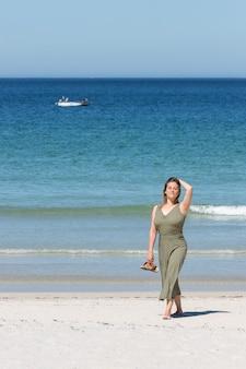 Femme blonde d'âge moyen dans une robe verte marchant pieds nus sur la plage