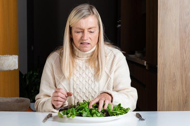 Femme blonde d'âge moyen avec une expression faciale insatisfaite de manger une salade dans la cuisine, une alimentation saine et un concept de régime