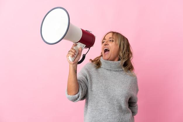 Femme blonde d'âge moyen sur fond rose isolé criant à travers un mégaphone pour annoncer quelque chose en position latérale