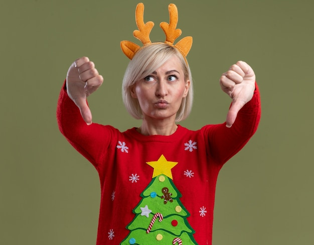 Femme blonde d'âge moyen insatisfaite portant un bandeau de bois de renne de noël et un pull de noël à côté montrant les pouces vers le bas avec des lèvres pincées isolé sur fond vert olive