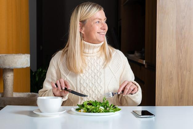 Femme blonde d'âge moyen mangeant de la salade dans la cuisine, concept d'alimentation saine