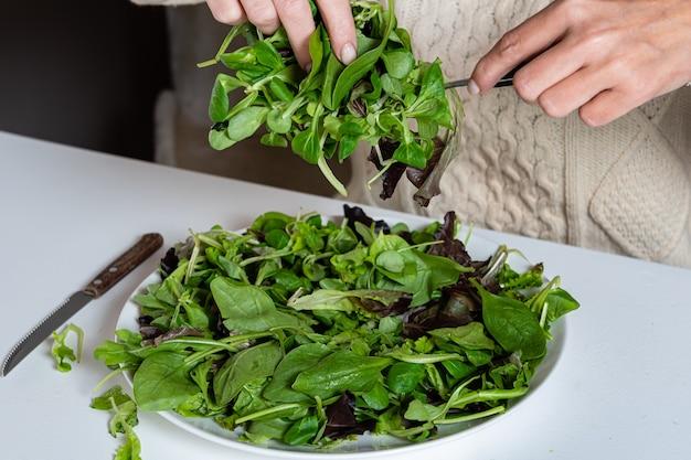 Femme blonde d'âge moyen, manger une salade dans la cuisine, concept d'aliments sains, gros plan