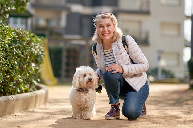Femme blonde d'âge moyen marchant avec un chien blanc moelleux dans la ville d'été.