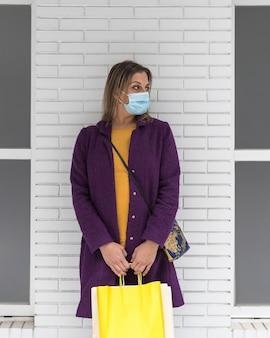 Une femme blonde d'âge moyen portant un masque chirurgical et tenant des sacs à provisions