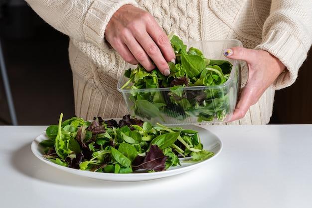 Femme blonde d'âge moyen préparant une salade verte dans la cuisine, une alimentation saine et un concept de régime, gros plan