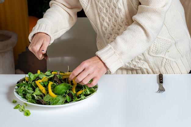 Femme blonde d'âge moyen préparant une salade verte dans la cuisine, concept d'alimentation saine et de régime alimentaire, gros plan
