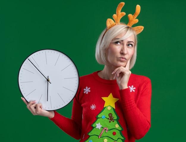 Femme blonde d'âge moyen réfléchie portant bandeau de bois de renne de noël et chandail de noël tenant horloge gardant la main sur le menton en levant isolé sur fond vert