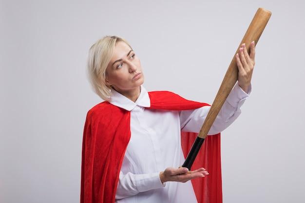 Femme blonde d'âge moyen réfléchie de super-héros en cape rouge tenant et regardant une batte de baseball isolée sur un mur blanc