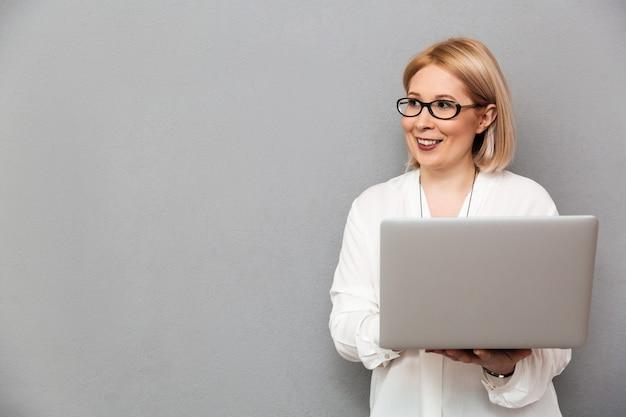 Femme blonde d'âge moyen souriante en chemise et lunettes