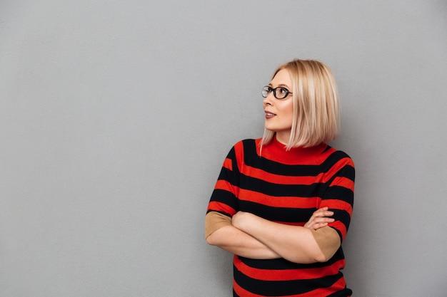 Femme blonde d'âge moyen souriante en pull et lunettes posant