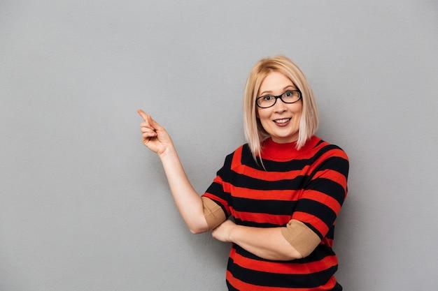 Femme blonde d'âge moyen souriante en pull et lunettes