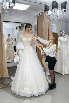 Femme blonde aidant la mariée dans la boutique de mariage
