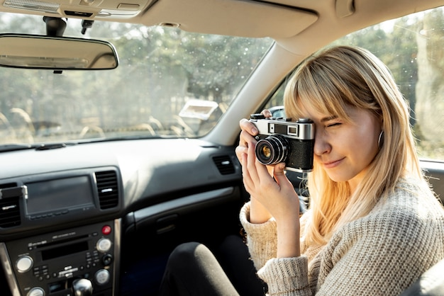 Femme blonde à l'aide d'un appareil photo vintage en voiture