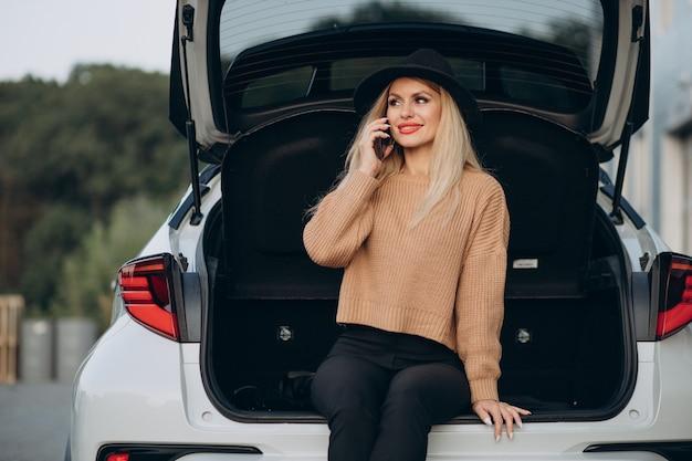 Femme blonde à l'aide de téléphone et assis dans le coffre de la voiture